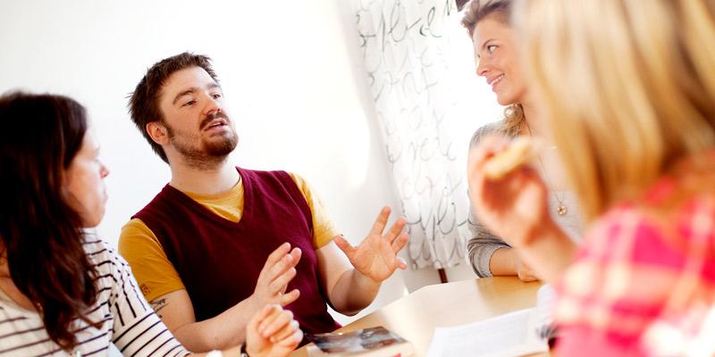Illustrasjonsbilde: mennesker i samtale rundt et bord.