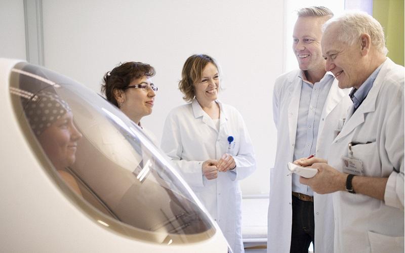 Helsepersonell/forskere observerer kvinne som får målt kroppssammensetning. Foto.