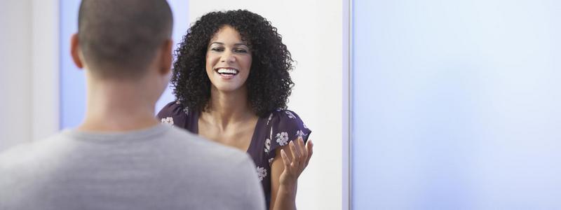 Smilende kvinne som snakker til en annen person. Foto.