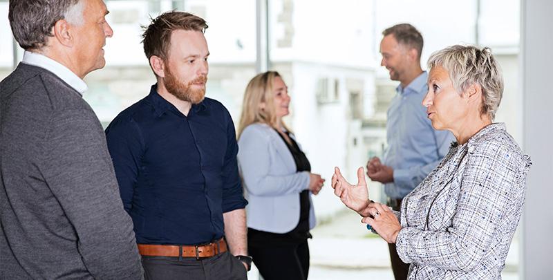 Tre menn og to kvinner i pene klær diskuterer. Foto.