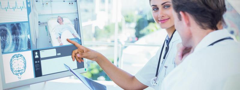 To helsearbeidere ser på dataskjerm med pasientovervåkning. Foto.