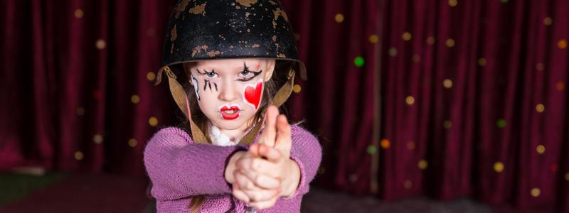 Barn med ansiktsmaling og kostyme foran sceneteppe. Foto.