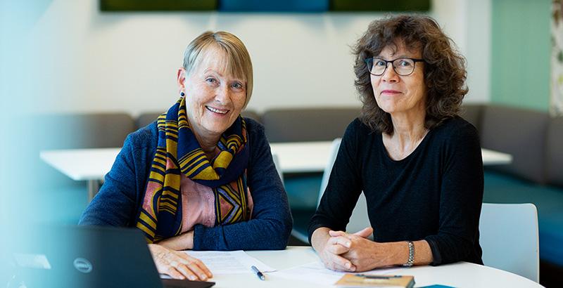 To kvinner sitter ved et bord og ser i kamera. Foto.