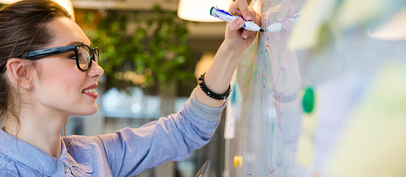 Forretningskvinne skriver på whiteboard