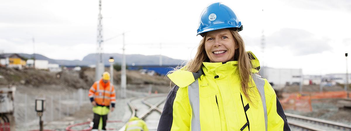 Illustasjonsbilde: Jernbaneanlegg med kvinne i hjelm og arbeidstøy i forgrunnen.