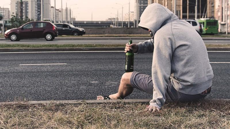 Gutt som sitter med flaske i veikanten