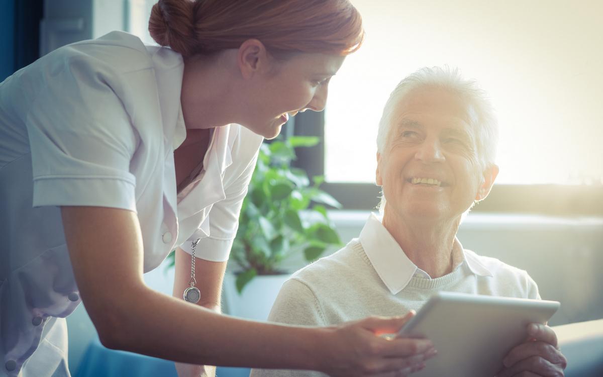 Helsearbeider og eldre mann med nettbrett. Foto.