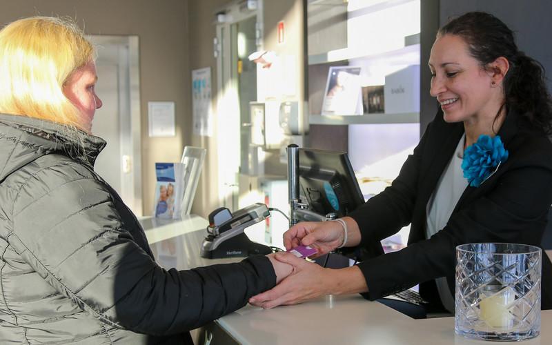 Kvinne viser hvordan en blind kvinne skal betale i en betalingsterminal. Foto.