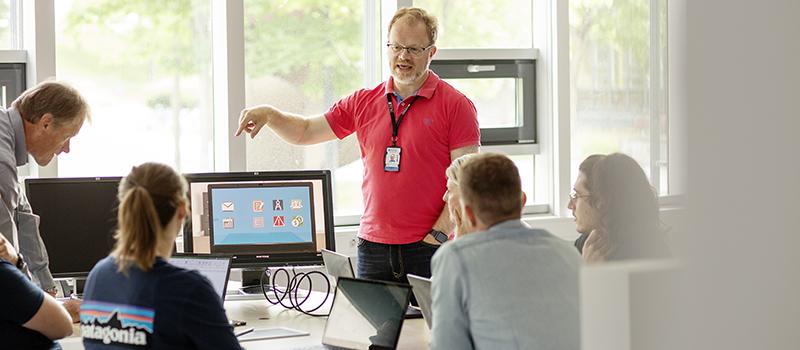 Gruppe studenter rundt et bord med datamaskin blir veiledet av lærer