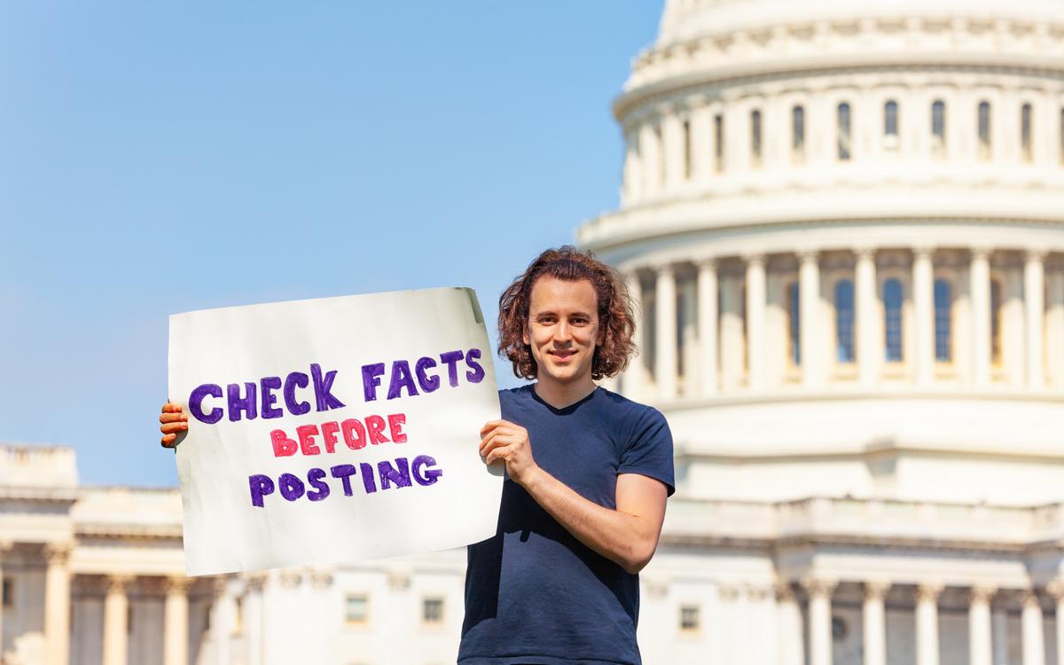 Mann står foran Captol med plakat med teksten