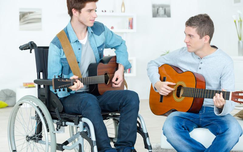 To unge menn spiller gitar sammen, den ene sittende rullestol.